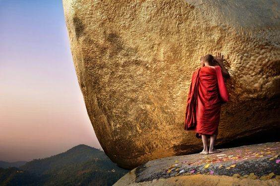 Monje budista rezando sobre la Golden Rock