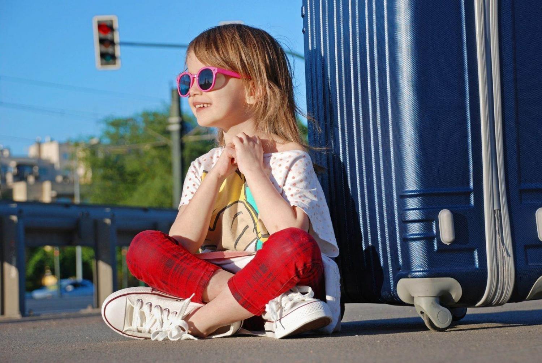 niña con gafas de sol sentada junto a una maleta