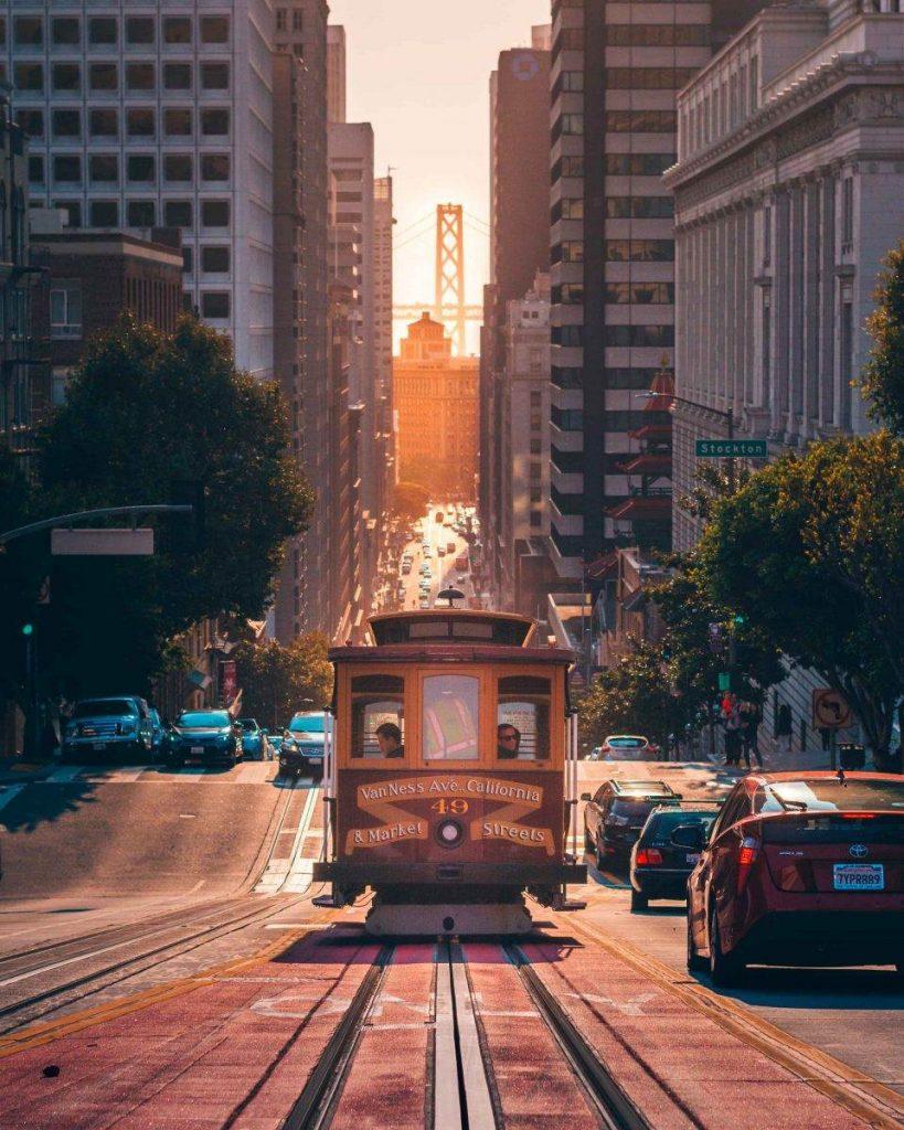 Tranvia en San Francisco junto a dos edificios con el atardecer de fondo