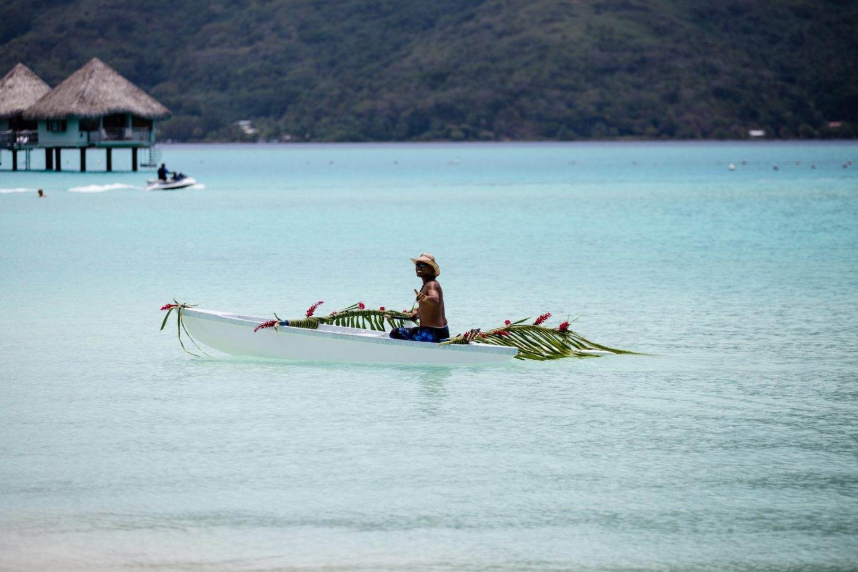 Tahitiano en una barca sobre aguas cristalinas