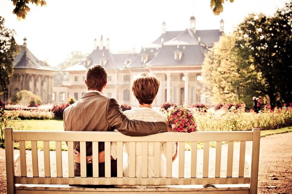 pareja frente a casa sentada en un banco
