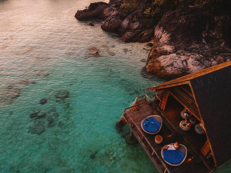 mujer sentada en una habitación de hotel sobre el mar en Bali