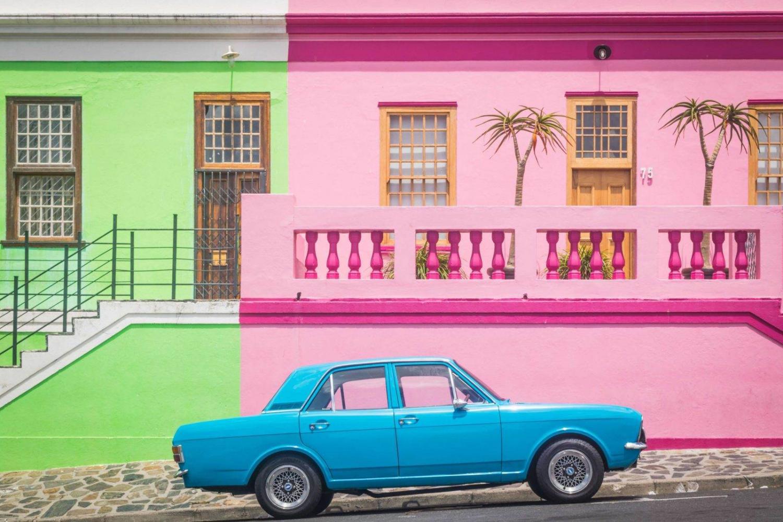 casas de color rosa y verde y un coche azul en ciudad del cabo