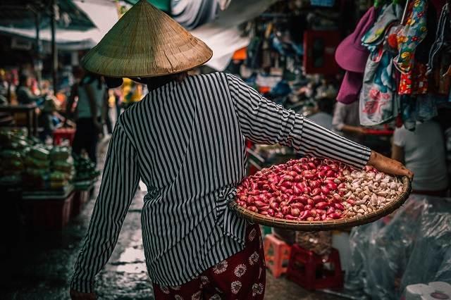 mujer vietnamita de espaldas con comida para comer en vietnam en un mercado de Hanoi
