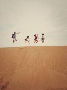 Familia dando un salto en una duna