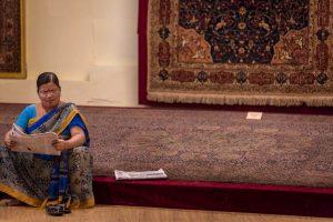 Mujer india sentada leyendo un periódico