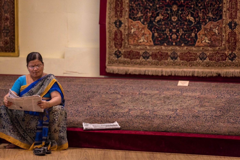 mujer hindú lee un periódico en una tienda de alfombras