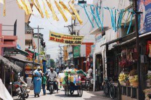 Calle con comercios abiertos en Delhi, India