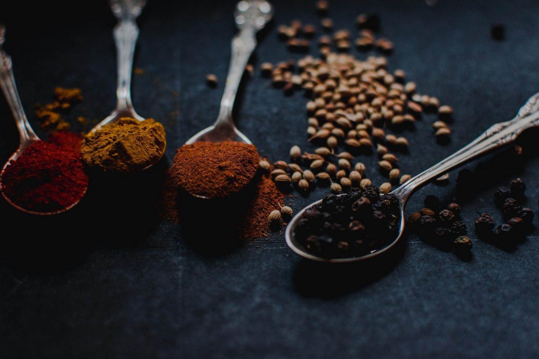 cuatro especias en su respectiva cuchara: pimentón, curry, canela y pimienta negra
