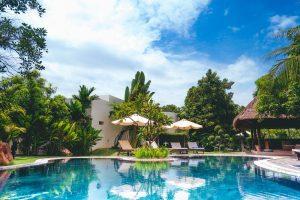 Piscina de un hotel con hamacas, sombrilla y gran vegetación