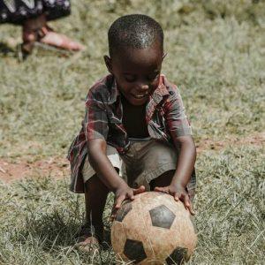 Niño negro jugando a la pelota