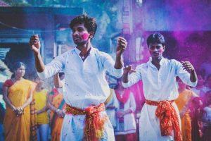 Hombres bailando en un desfile de colores en Delhi