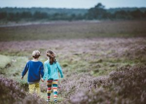 Niños de la mano de espaldas por el campo