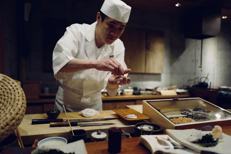 Cocinero japonés preparando sushi