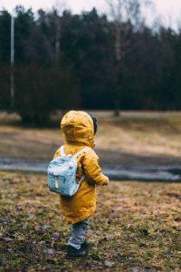 Niño de espaldas con chaquetón amarillo y mochila vaquera en el campo