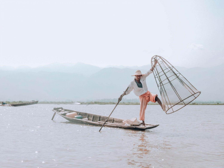 Pescador haciendo equilibrio sobre una barca en el lago Inle