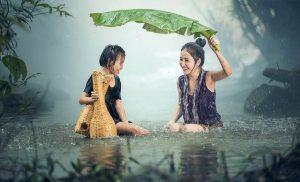 dos mujeres juegan bajo la lluvia en un río de Vietnam