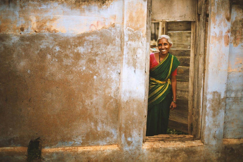 Mujer hindú sonriendo en la puerta de su casa