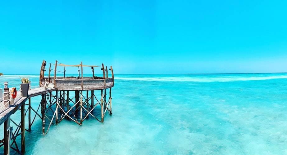 Muelle de madera sobre aguas cristalinas en Zanzíbar